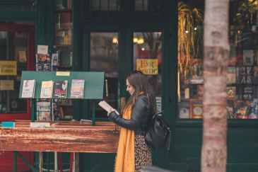 woman reading book near store